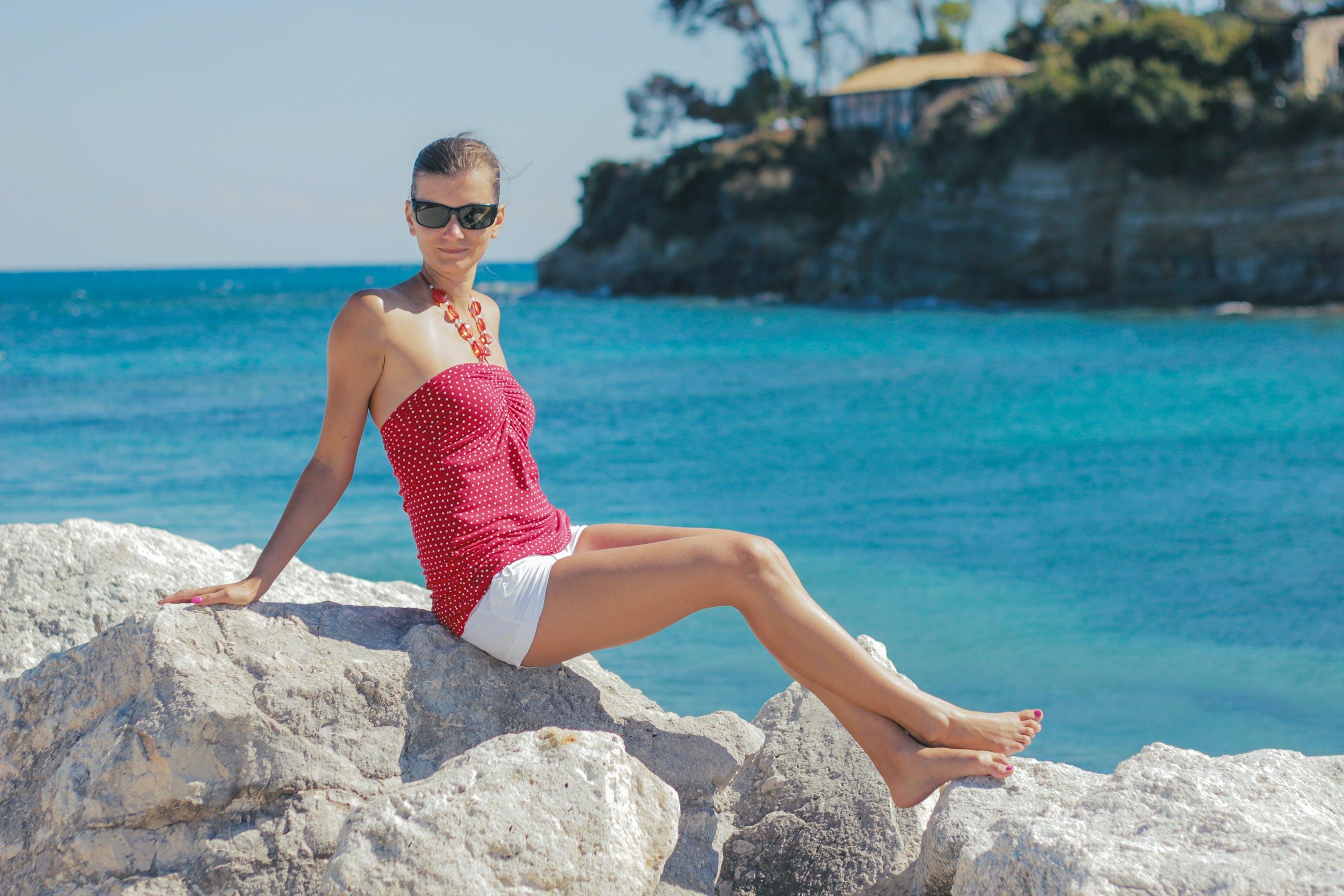 Woman Sitting on Gray Rock