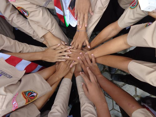 Crop military ethnic females stacking hands