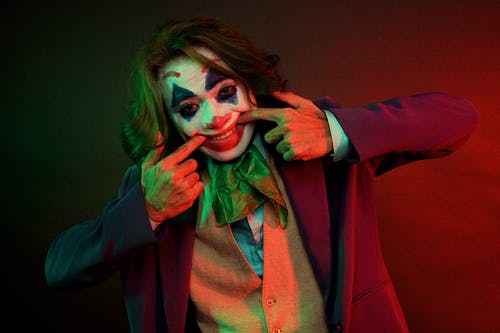 Dramatic male clown with painted face grimacing smile pulling mouth with hands while looking at camera