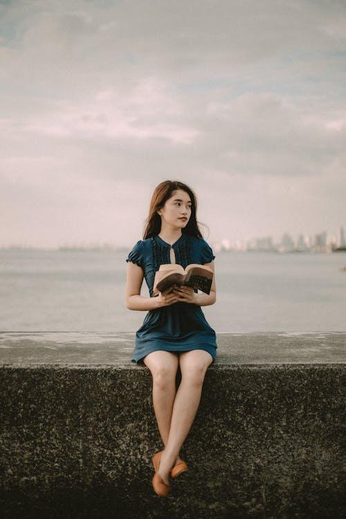 Fotografia Com Foco Seletivo De Mulher Sentada Segurando Um Livro Aberto
