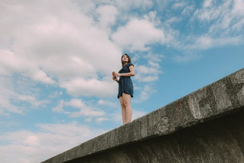 Low Angle Photo of Woman Standing on Bridge