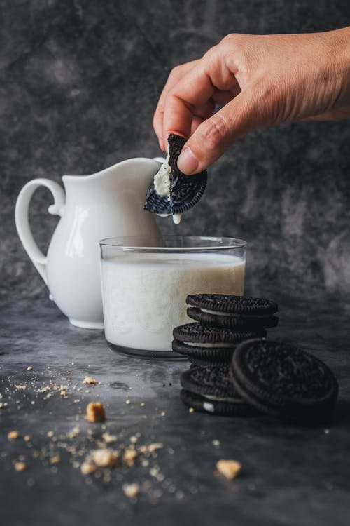 Person Holding Piece of Biscuit With Milk in Glass