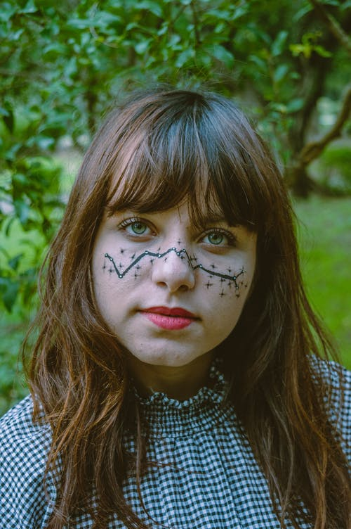 Teen girl with painted face standing near green plants