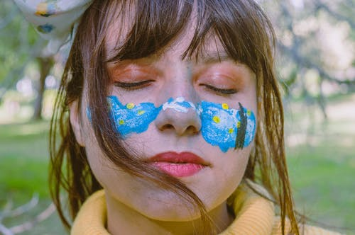 Crop serious teen girl with closed eyes and colorful paint on face standing near greenery