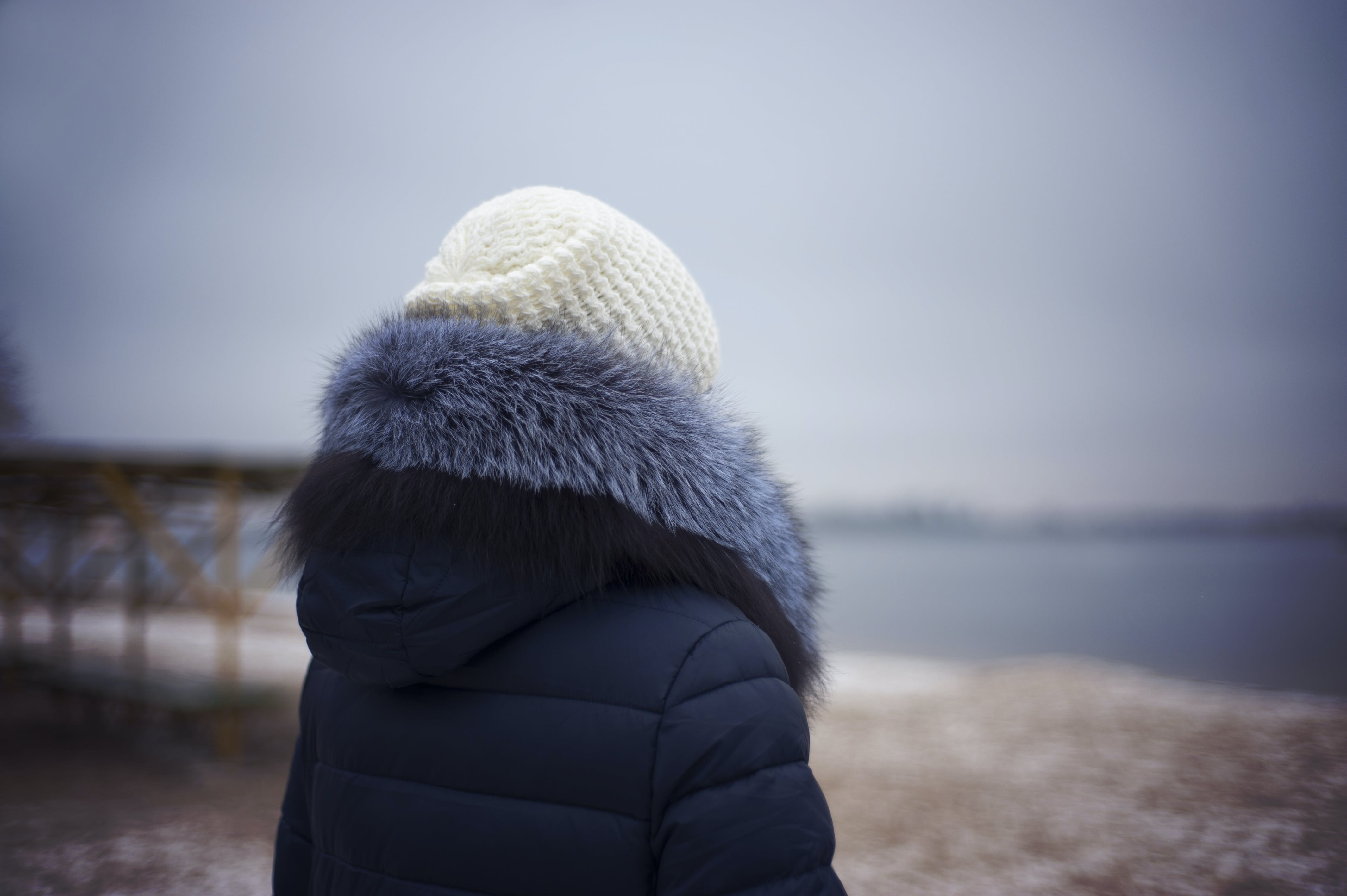 Woman Wearing Blue Parka Jacket and White Knit Cap