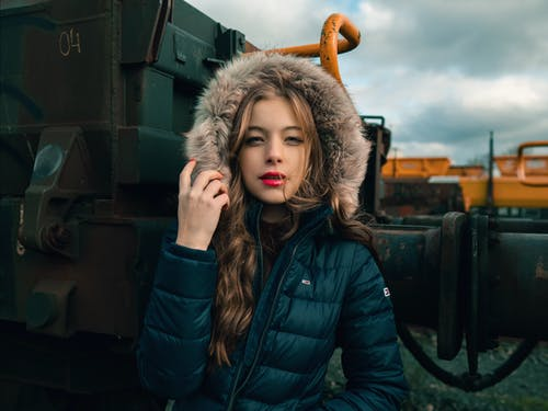 Young woman in warm clothes standing near train