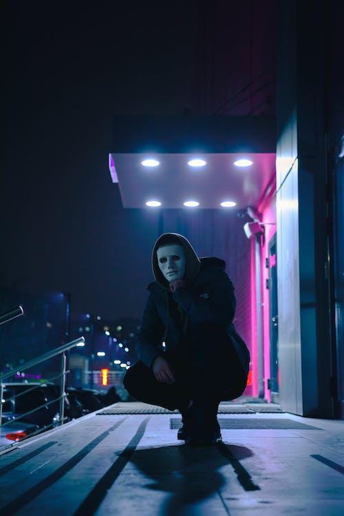 Crouching Man Wearing Black Hoodie at Night