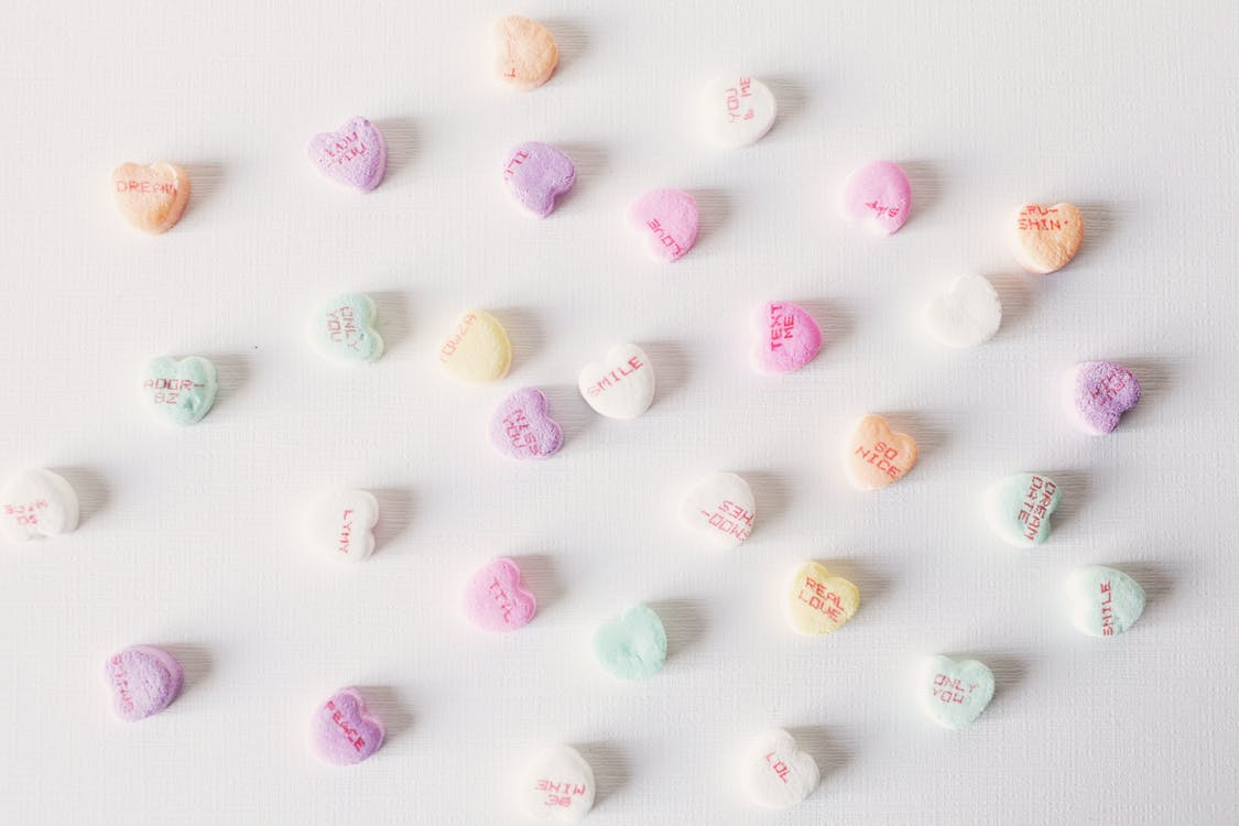 Top view composition of multicolored small heart shaped sweets placed on plain white surface