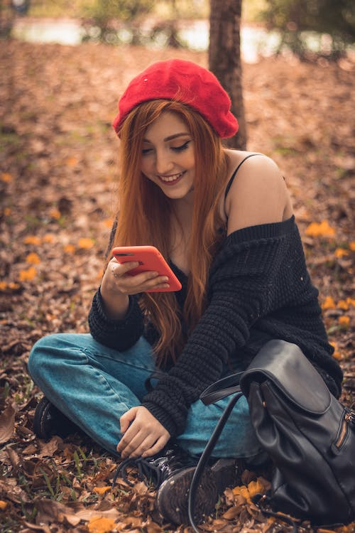 Selective Focus Photography of Sitting and Smiling Woman Using Smartphone