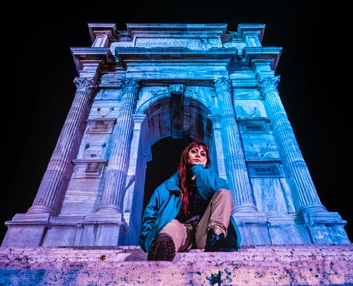 Woman in Blue Jacket Sitting Beside Arco di Traiano