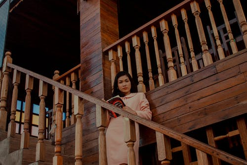 Woman Holding Book Standing on Staircase