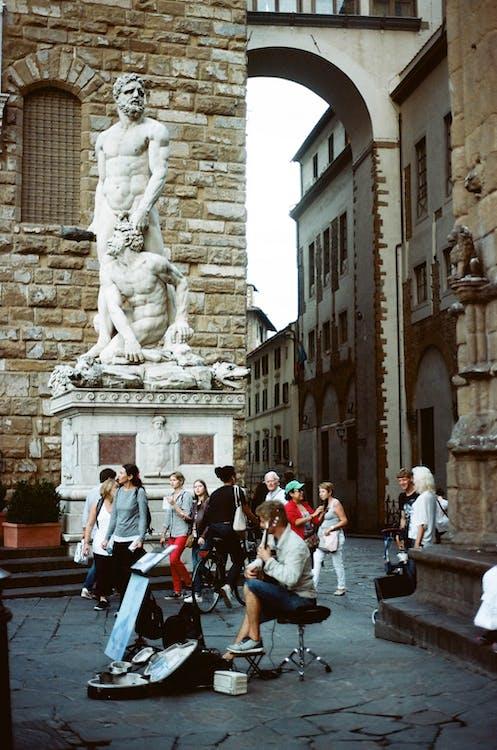 People Walking on Sidewalk Near Statue of Man and Woman