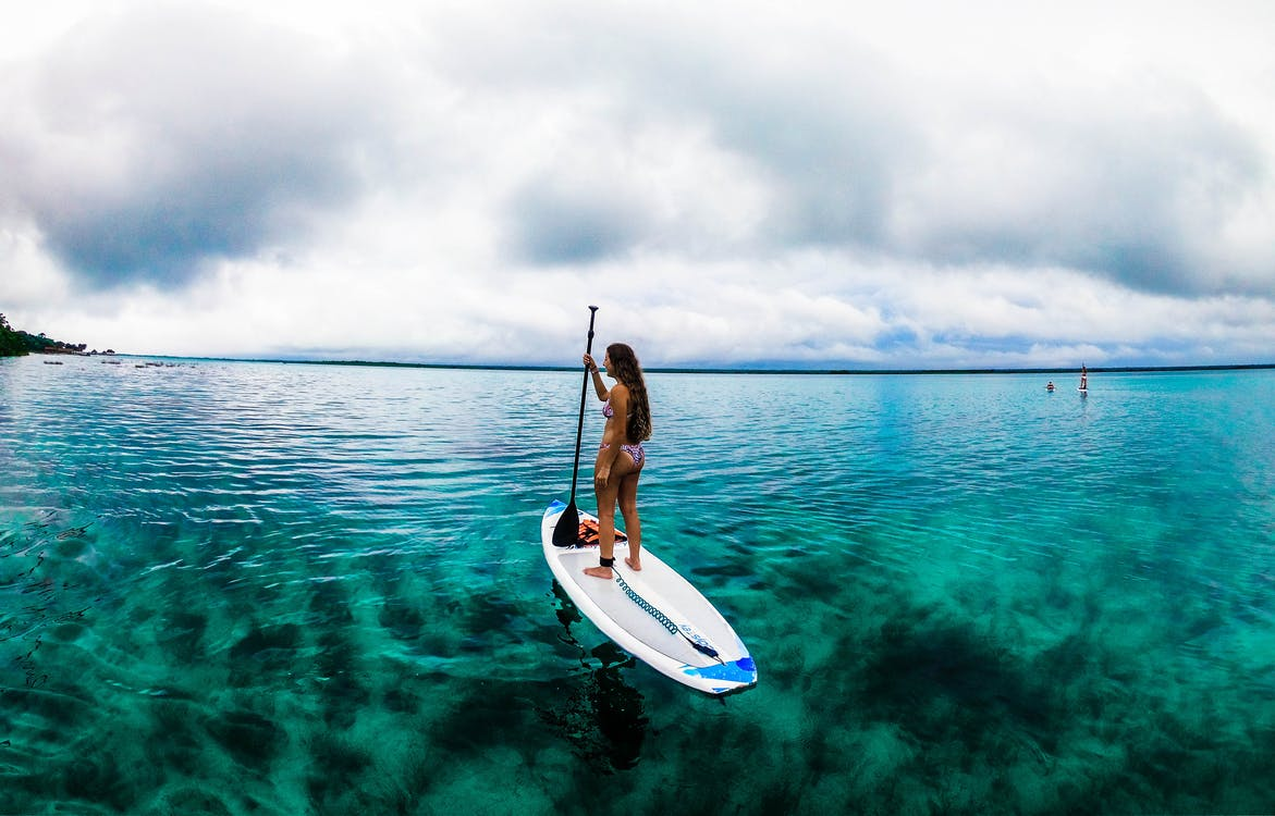 woman standing on paddle board on perfect water