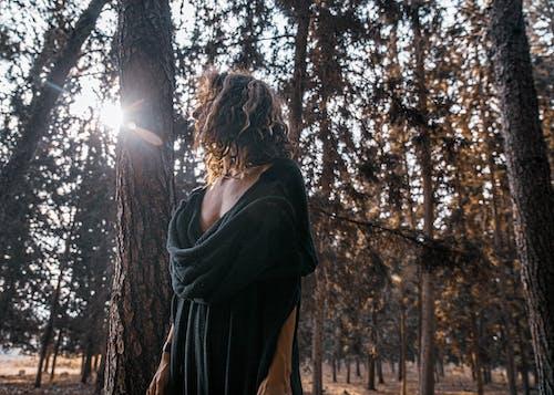 Woman in Black Dress beside a Tree