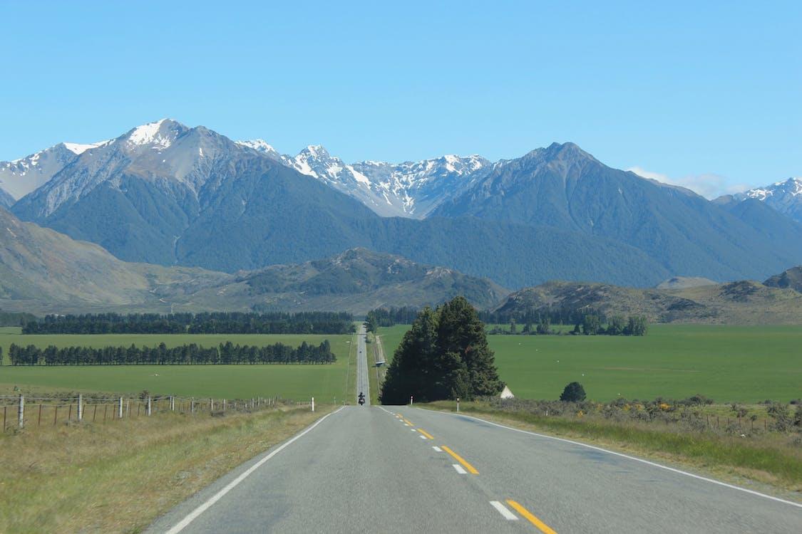 Foto profissional grátis de estrada, grama, montanhas