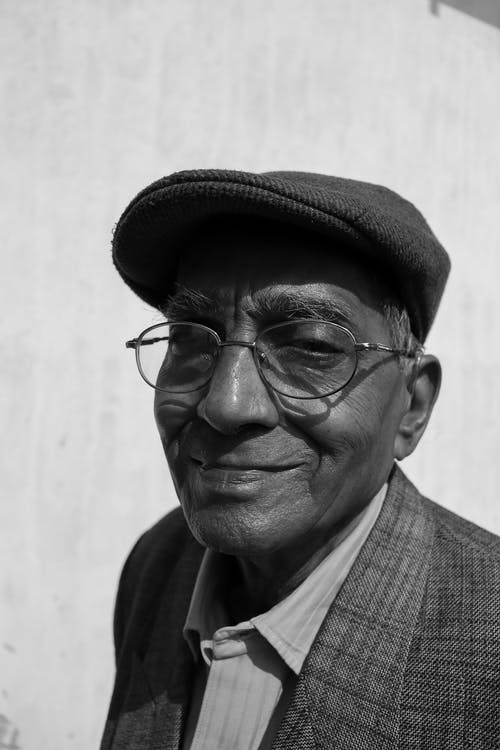 Grayscale Photography of Smiling Man Wearing Hat
