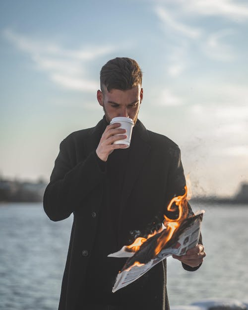 Man Holding Burning Paper