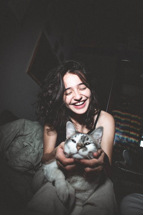 Selective Focus Photography of Smiling Girl Holding Cat