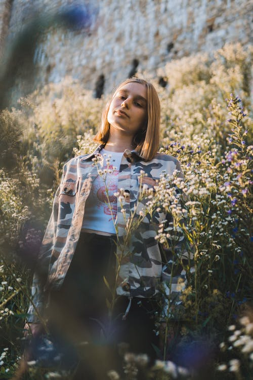 Photo Of Woman Standing Near Flowers