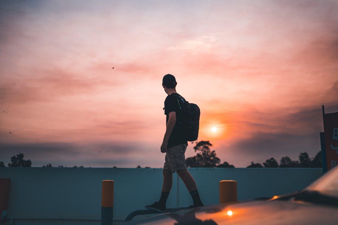 Man Walking on Metal Pipe Near the Road