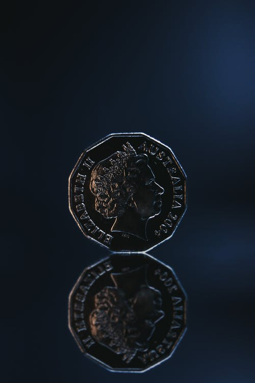 Reflection of old coin placed on blue background