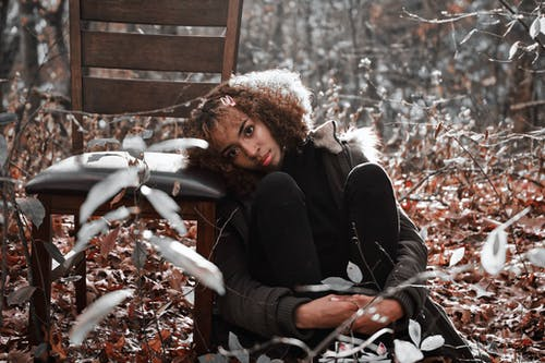 Woman with Curly hair Resting Her Head on Wooden Chair