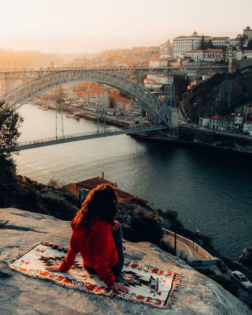 Woman Sitting on Cliff Overlooking Bridge