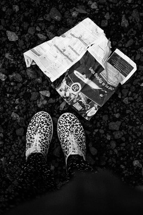 Grayscale Photography of Person Beside Flyer on Ground