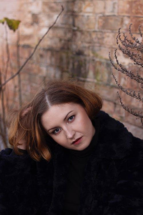 Kobieta Siedzi W Pobliżu Brązowej ściany