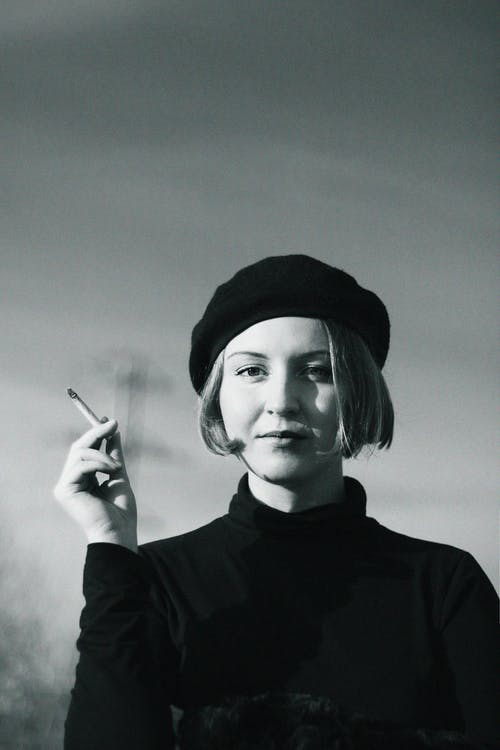 Grayscale Photography of Woman Holding Cigarette