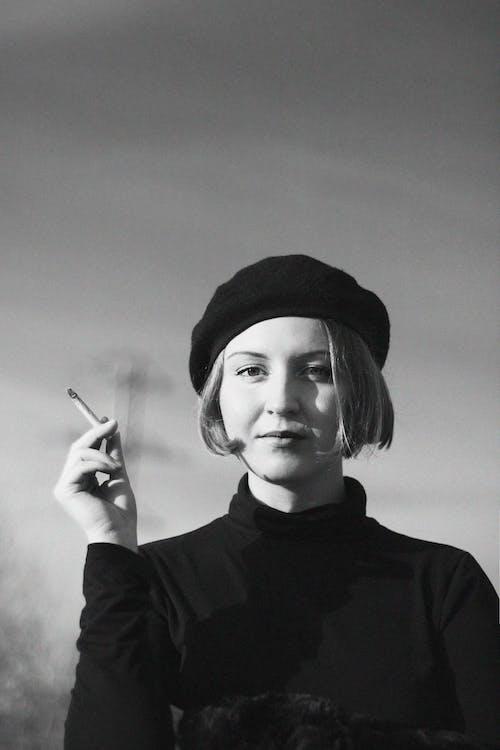 Fotografia W Skali Szarości Przedstawiająca Kobietę Trzymającą Papierosa