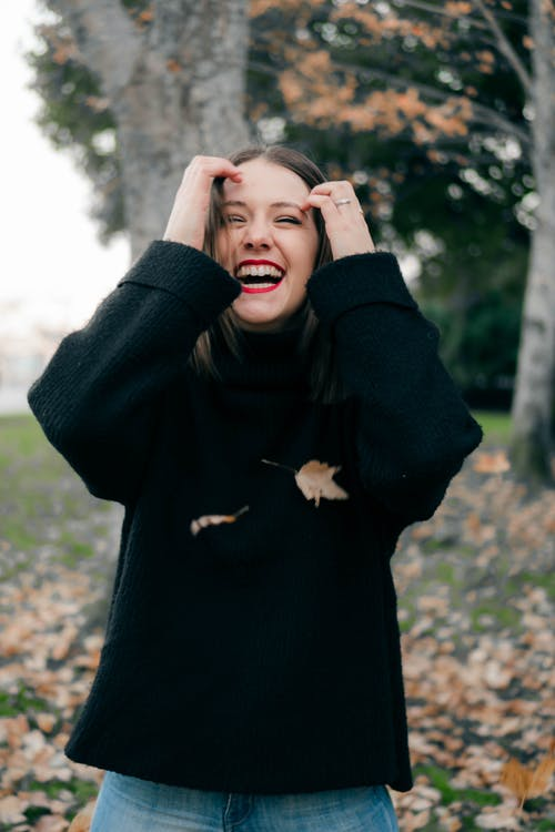 Woman Wearing Black Sweater With A Happy Face