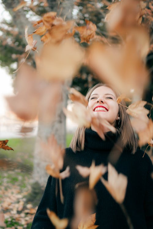 Photo Of Woman Standing Under Falling Leaves