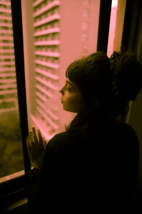 Woman Standing Beside Window Looking Out