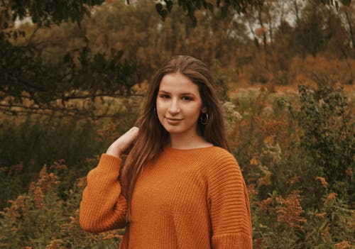 Woman in Brown Knit Sweater Standing Near Plants