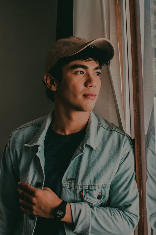 Man Wearing Cap and Denim Jacket Looking Out the Window