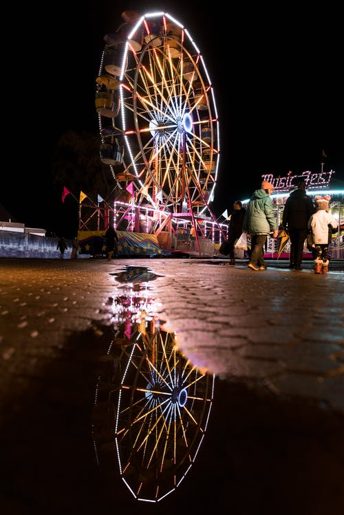 Lighted Ferris Wheel Reflection on Water Puddle at Night
