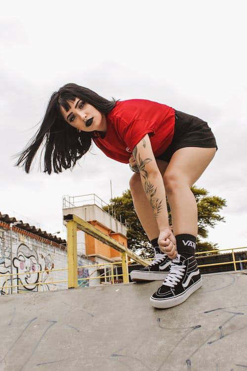 Woman in Red T-shirt, Black Short-shorts, and Black Vans Sk8-hi Sneakers