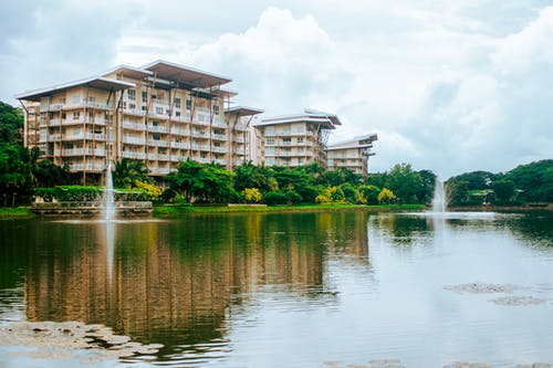 Complex of modern buildings located on shore of rippling lake with fountains surrounded by lush green trees against cloudy sky in Philippines