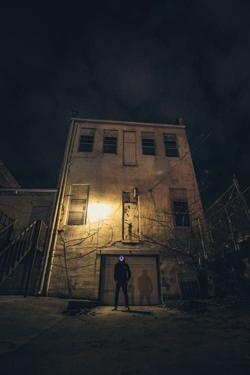 Man Standing in Front of Building during Nighttime