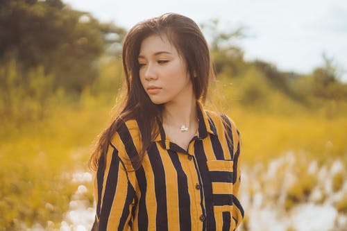 Woman in Orange and Black Striped Collared Shirt on Grass Field