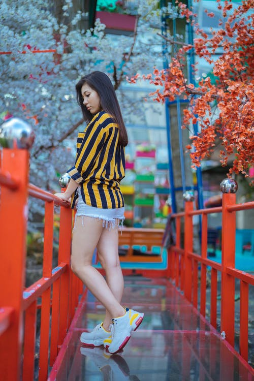 Woman IN  Black and Yellow Striped Shirt Standing On A Bridge