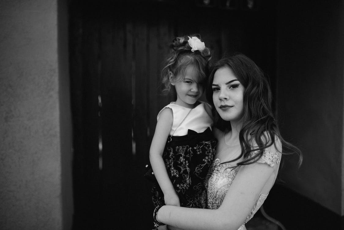 Grayscale Photo of Woman Carrying Girl