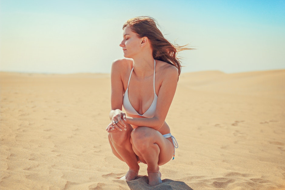 Young Woman Sitting on Sand at Beach