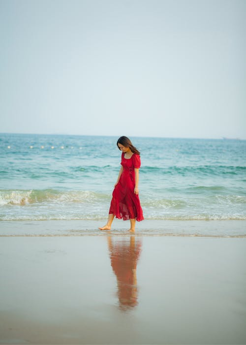 Woman Wearing Red Dress While Walking at Beach