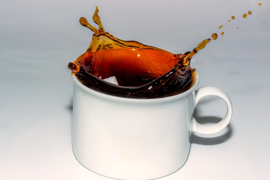 Coffee Splashing in Cup Against White Background