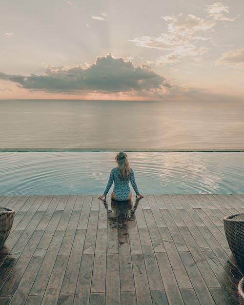 Женщина, сидящая у бассейна