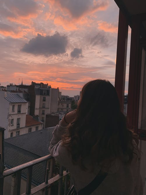 Woman admiring bright cloudy sunset