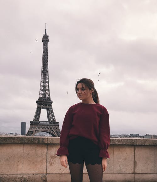 Woman in Red Long Sleeve Shirt Standing Near Eiffel Tower