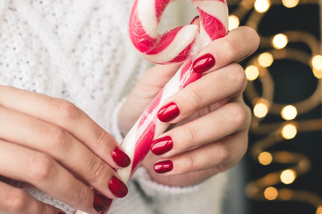 Close-Up Photo of Person Holding Candy Cane